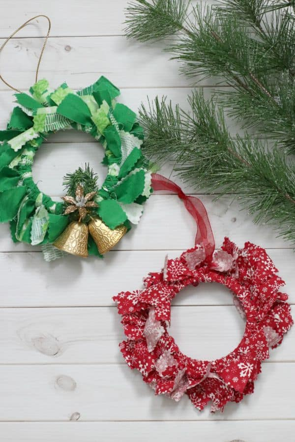 Two fabric mason jar lid ornaments (one green and one red) on a white plank table next to a green bough.