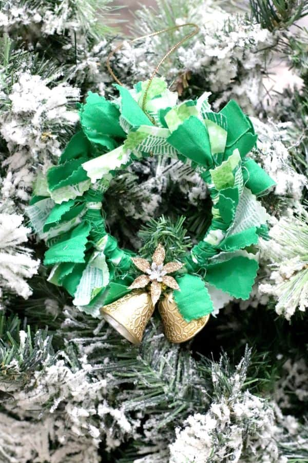 Festive wreath-like ornament made from fabric and a mason jar lid ring with added jingle bell embellishment, hanging on a frosted tree.