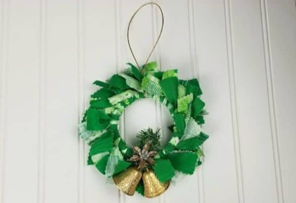 a green fabric mason jar lid ornament with gold bells at the bottom of it on a white background