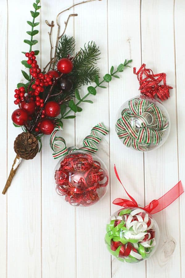 three clear ornaments filled with curled ribbon and topped with a curled ribbon bow on a white wooden table next to a holly berry sprig