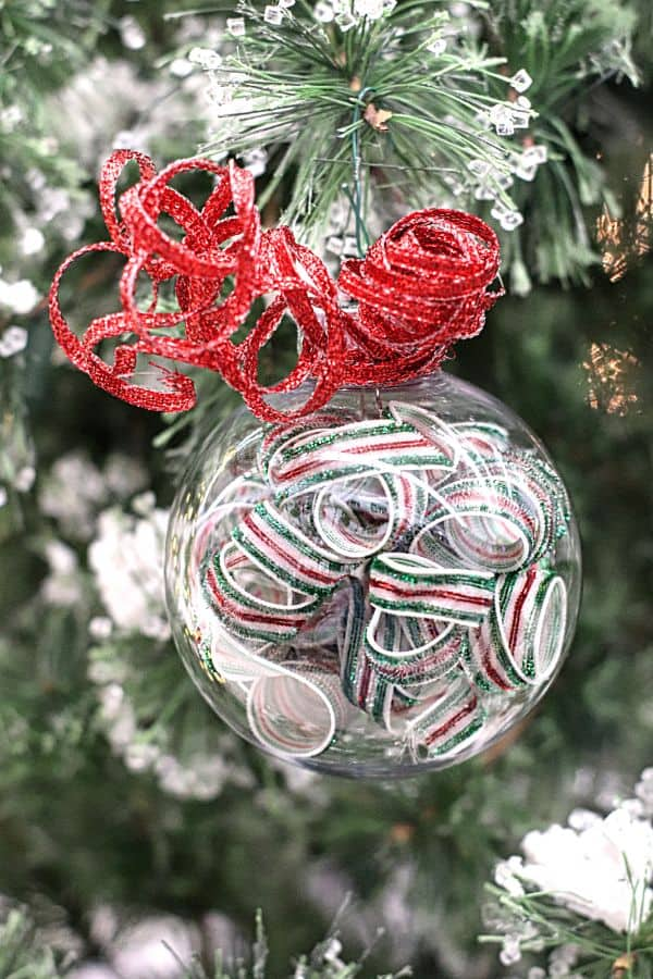 a clear ornament filled with curled ribbon with a red ribbon curl on the top hanging from a Christmas tree