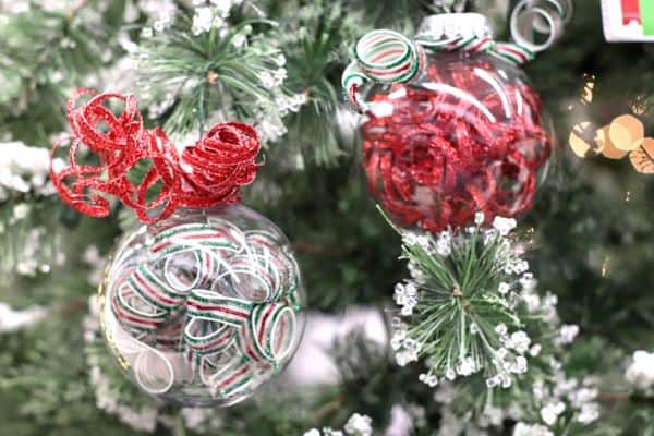 two clear ornaments filled with curled ribbon with a red and green ribbon curl on the top hanging from a Christmas tree