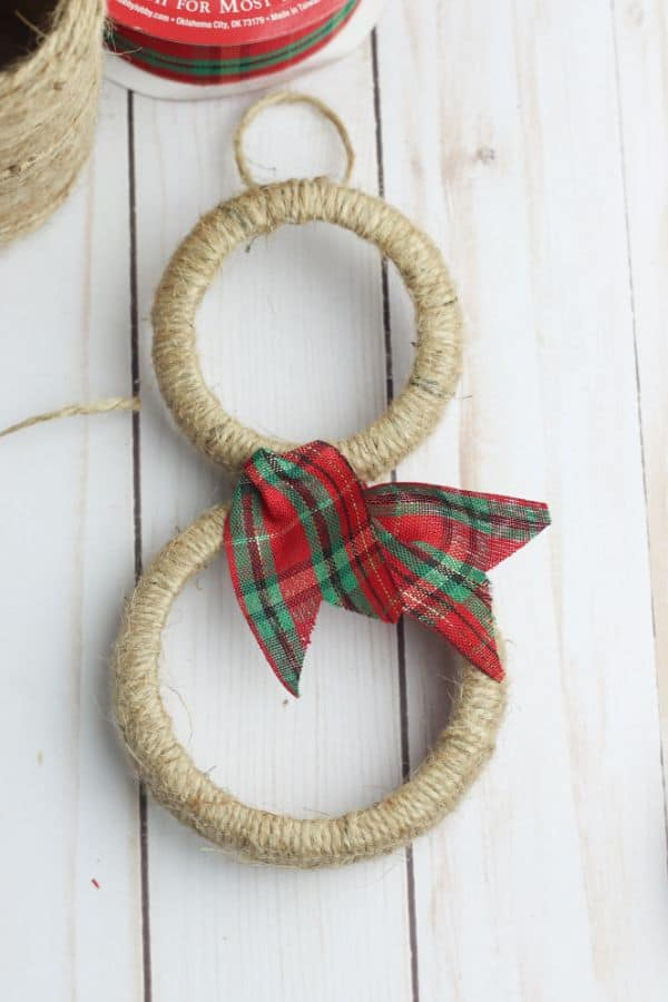 mason jar lids wrapped in twine and decorated with a red and green ribbon to look like snowmen ornaments next to more twine and a red and green ribbon on a white wood table