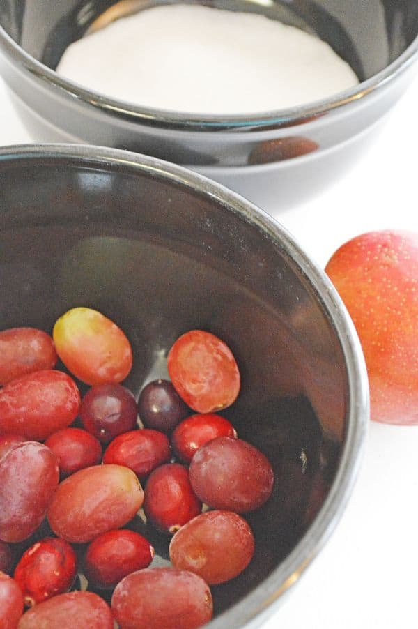 cranberries and grapes in a metal bowl next to another bowl of sugar next to a plum