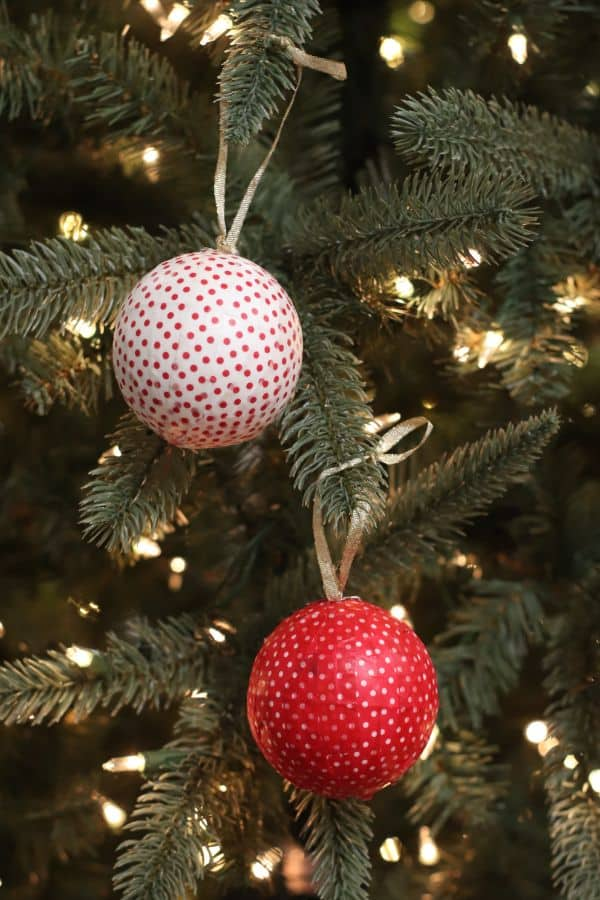 two ornaments wrapped with red and white washi tape hung with  gold ribbon from a  Christmas tree