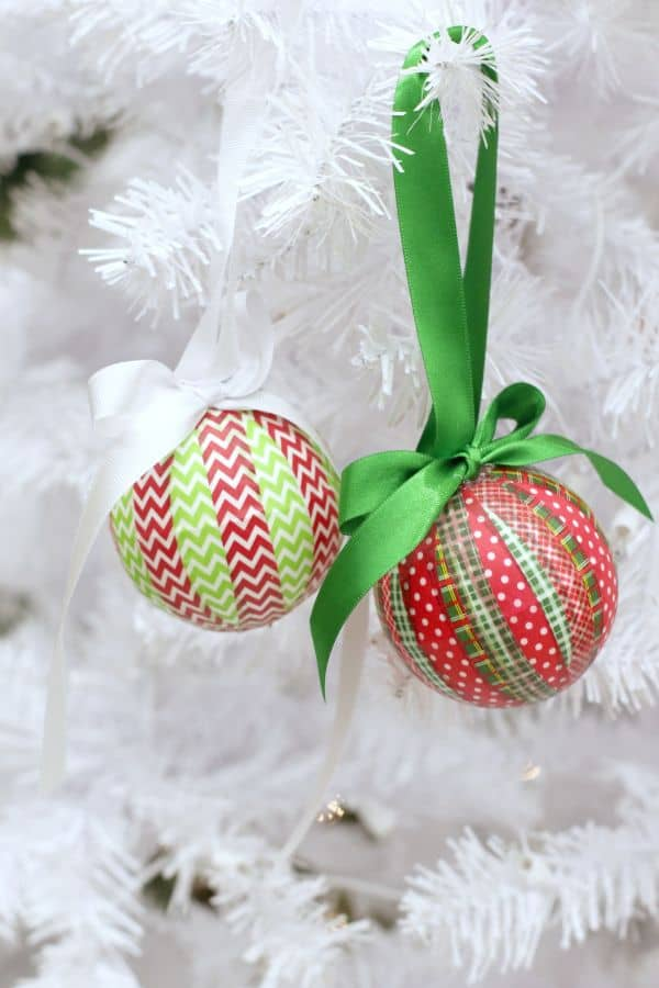 two ornaments wrapped with red and green patterned washi tape hung on a white Christmas tree