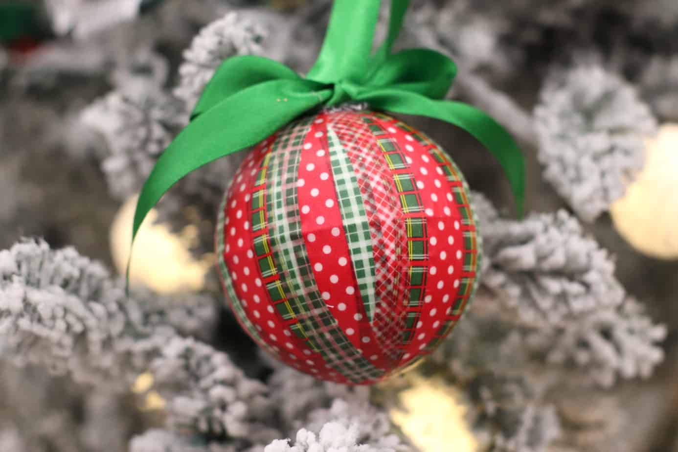 on ornament wrapped with red and green washi tape hung with a green ribbon from a flocked Christmas tree