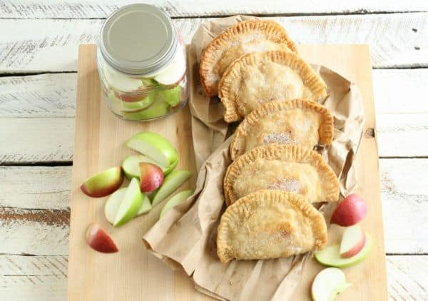 apple hand pies on a brown paper bag on a brown cutting board next to apple slices on the board and in a glass jar