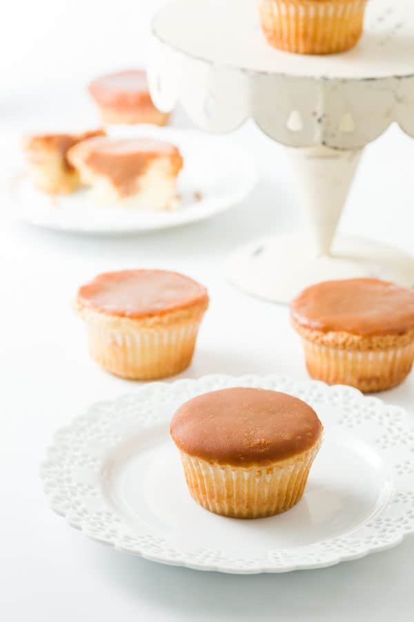 cupcakes with caramel icing on a white plate, white table and white cake plate