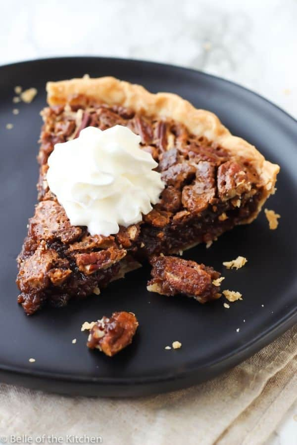 chocolate pecan pie topped with whipped cream on a black plate