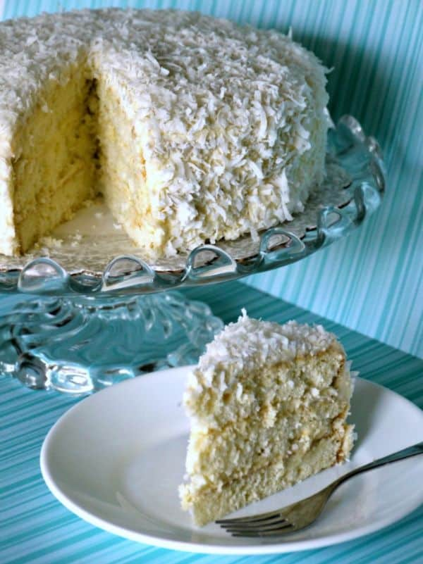 a slice of coconut cake on a white plate with a fork on it next to the rest of the cake on a glass cake plate on a blue background