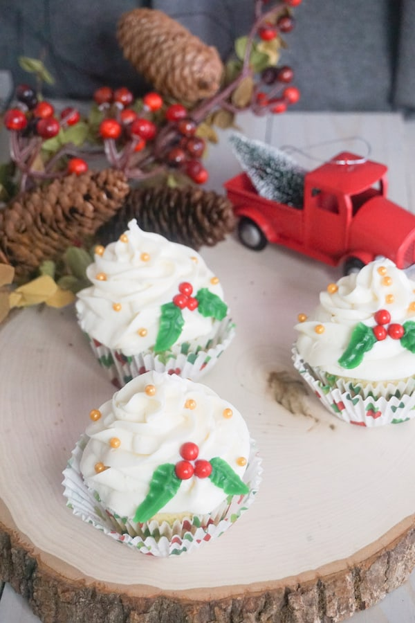 3 cupcakes topped with white frosting, yellow dot candy, green frosting and red candy to look like holly berries all on a log next to a red toy truck with pinecones in the background