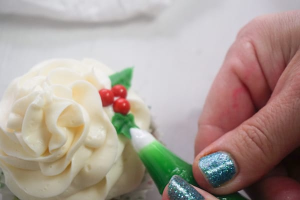 a hand placing green frosting next to red candies to look like holly berries on a cupcake topped with white frosting