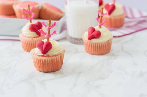 pink cupcakes topped with white frosting, a red heart, and a pretzel stick with pink frosting made to look like an arrow, all on a white counter with more cupcakes and a glass of milk in the background