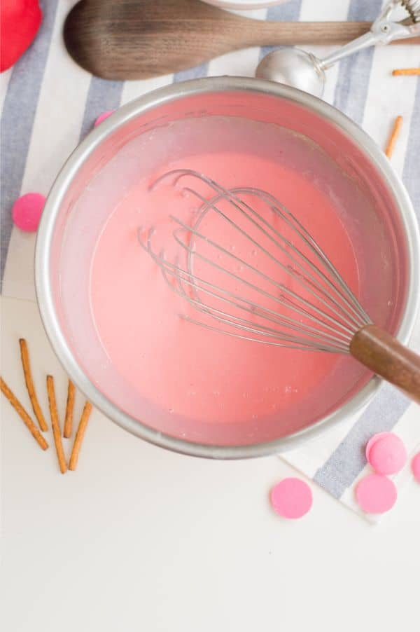 pink cake batter in a metal mixing bowl with a whisk in it next to a wooden spoon, pretzel sticks and pink candy melts on a blue and white striped cloth on a white table