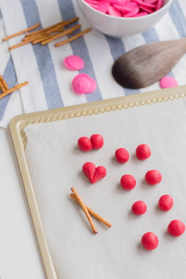 a white bowl with pink candy melts next to more of the same and pretzel sticks, a wooden spoon, and red fondant being shaped into balls and a heart on a baking sheet lined with parchment paper on a blue and white striped cloth on a white table