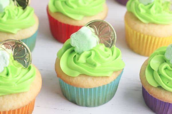 white cupcakes decorated with green frosting, a shamrock marshmallow and gold coin, on a wood table