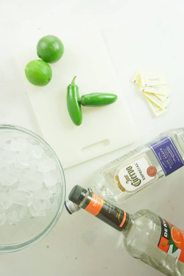 2 limes and 2 jalapeno peppers on a white cutting board next to packets of splenda, bottles of triple sec and tequila, and a glass bowl of ice on a white table