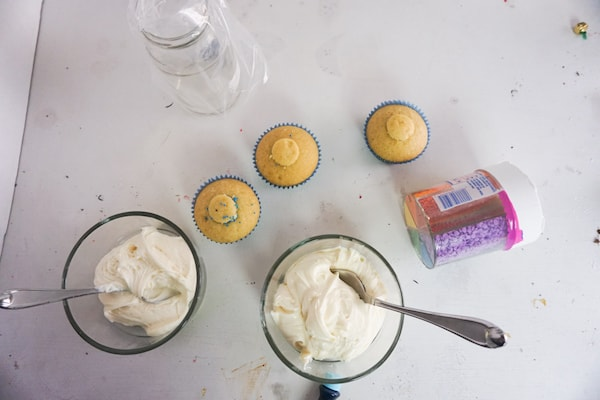 three cupcakes, a jar of sprinkles, two glass bowls of frosting with spoons in them