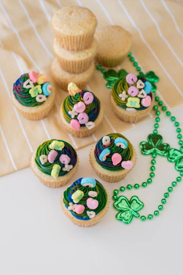 overhead view of vanilla cupcakes with multi-colored frosting topped with lucky charms marshmallows next to green shamrock beads on a tan linen with stacked vanilla cupcakes in the background