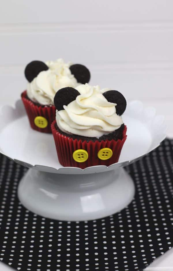 chocolate cupcakes decorated with white frosting, mini oreos, and two yellow buttons on the red cupcake liner, to look like Mickey Mouse, all on a white cake plate on a black and white polka dot cloth on a white background