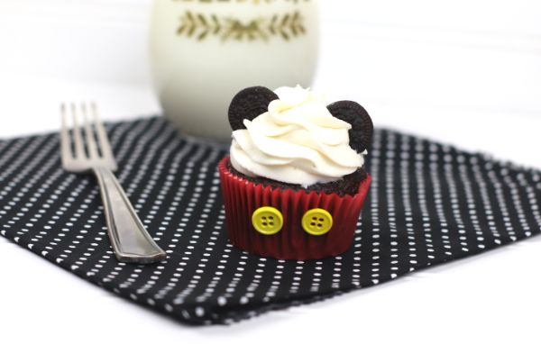 chocolate cupcake decorated with white frosting, mini oreos, and two yellow buttons on the red cupcake liner, to look like Mickey Mouse,  on a black and white polka dot cloth on a white background next to a fork and a glass of milk