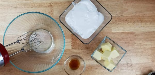 a glass mixing bowl with a mixer in it next to glass bowls of vanilla, butter and marshmallow fluff on a brown table