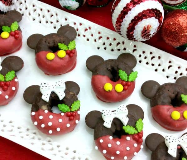 doughnuts decorated with red and brown frosting to look like mickey and minnie mouse christmas on a white platter on a red cloth with ornaments in the background