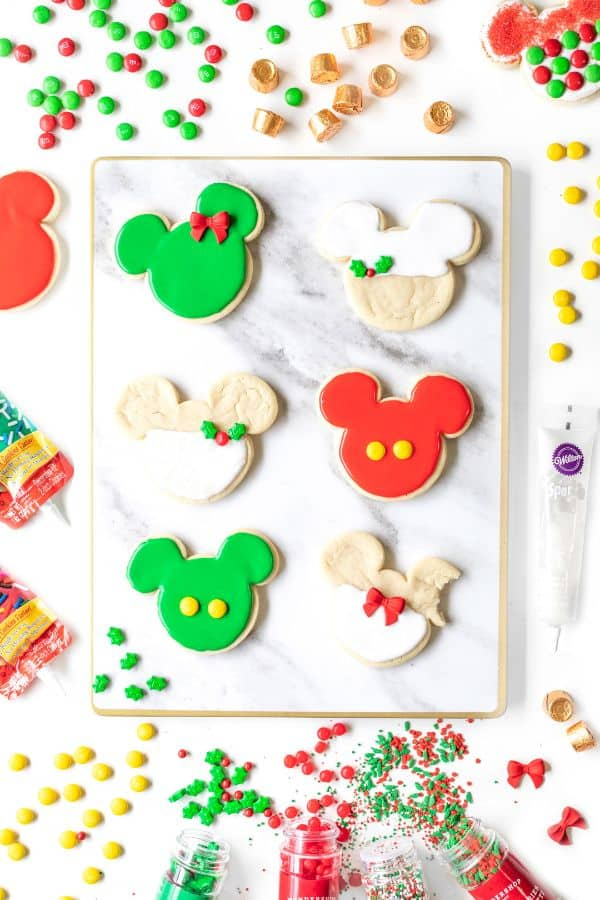 mickey christmas cookies with white, red and green frosting on a white background with frosting and sprinkles around it