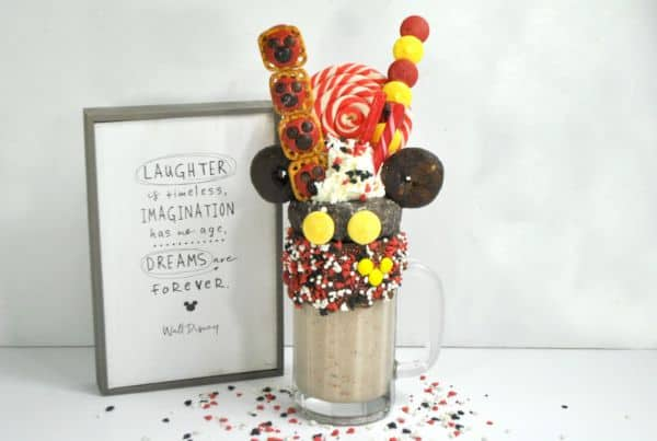 mickey mouse milkshake  next to a frame with words on it reading laughter of timeless imagination has no age dreams have forever on a gray background