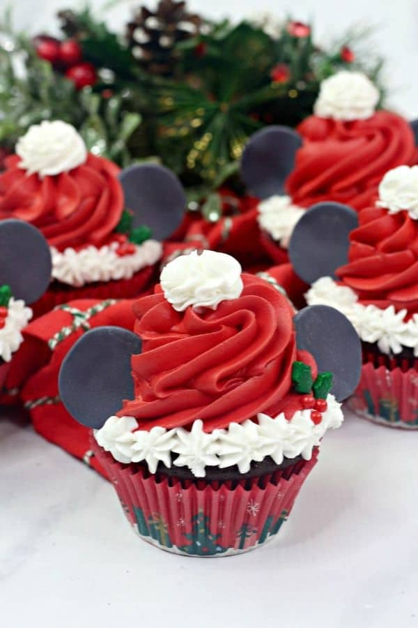 cupcakes decorated with red and white frosting to look like mickey mouse santa on a white counter