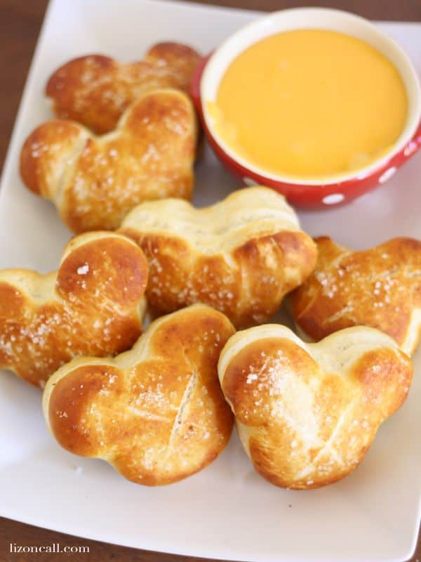 mickey mouse soft pretzels next to a bowl of dipping sauce on a white plate