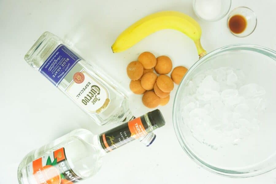 bottles of tequila and triple sec, vanilla wafers, banana, sugar, vanilla extract and ice in glass bowls, all on a white background