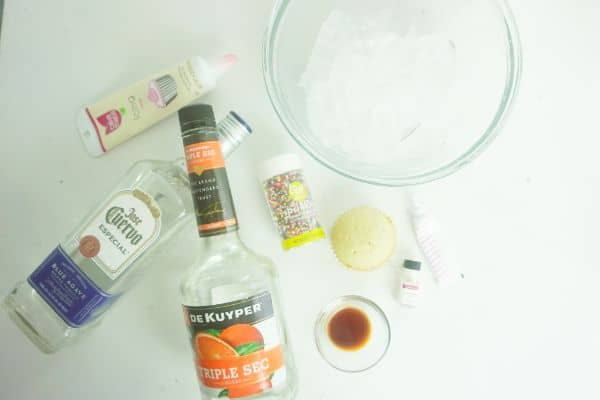 tequila, triple sec, cupcake, pink food coloring, cake batter oil, sprinkles, corn syrup and ice on a white background