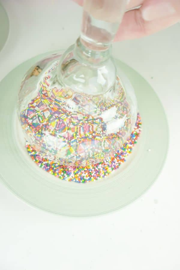 margarita glass being rimmed with sprinkles on a plate