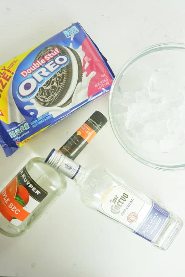 double stuff oreos, glass with ice in it, bottles of tequila and triple sec, all on a white background