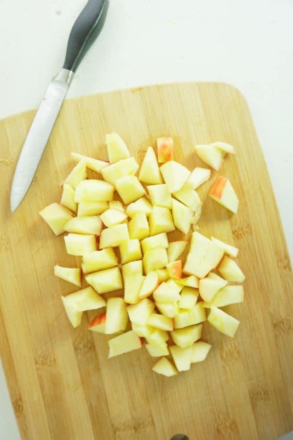 cubed apples on a wooden cutting board next to a knife