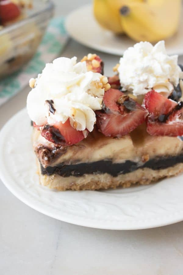 closeup view of a slice of banana split cake on a white plate on a white table with more cake in a glass baking dish and bananas on a white plate in the background