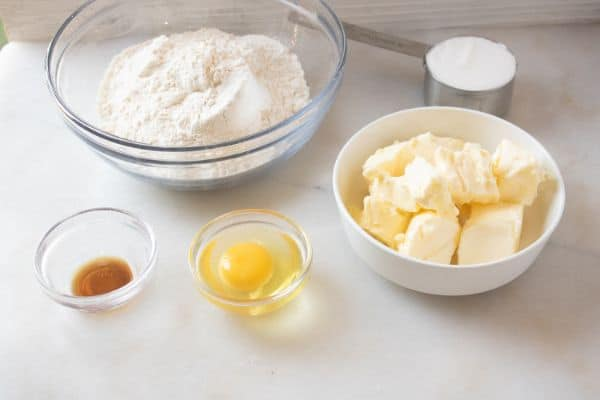 glass bowls of flour, vanilla extract and an egg, metal measuring cup of sugar, and butter in a white bowl on a white counter