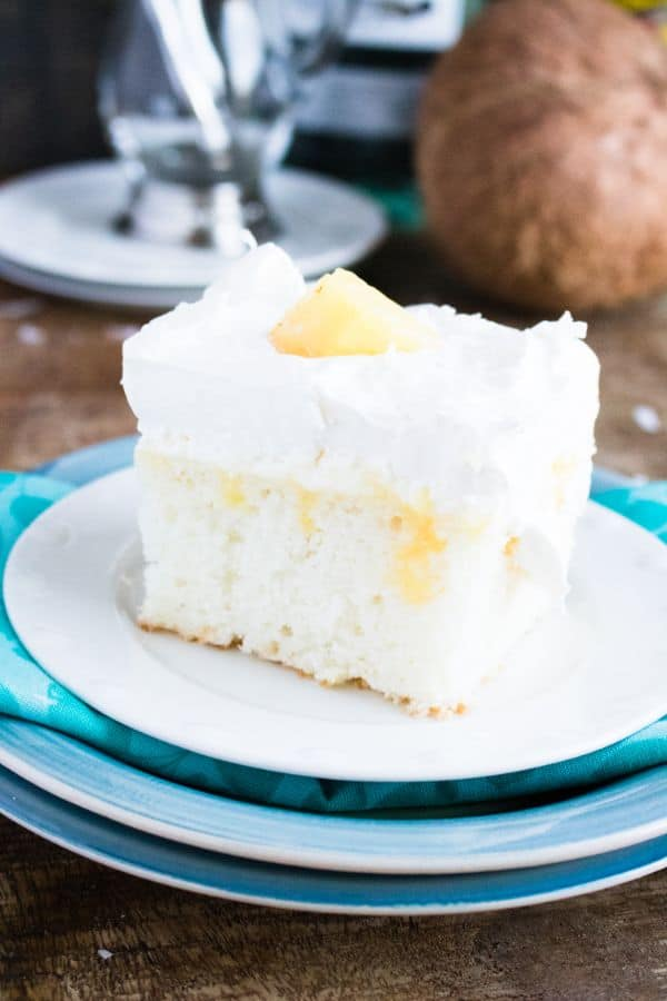 a slice of Boozy Pina Colada Cake on a plate on a brown table with a coconut in the background