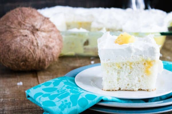 a slice of Boozy Pina Colada Cake on a plate on a brown table with more cake in a glass baking dish and a coconut in the background