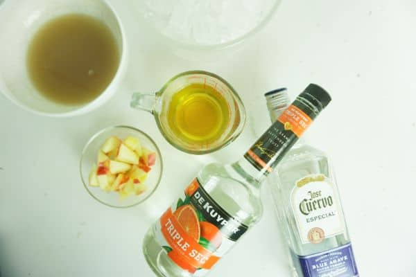 bottles of triple sec and tequila, apple juice, ice, apple slices, caramel sauce on a white background