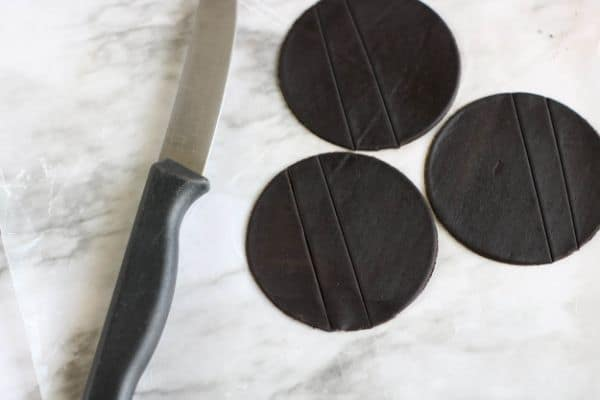 three circles of black fondant next to a knife on a gray counter