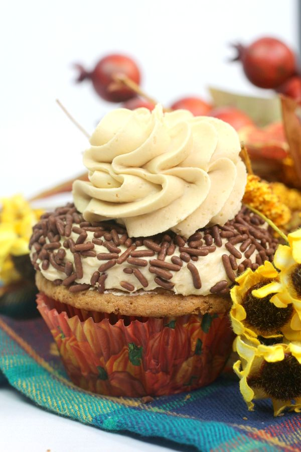 closeup of a Pumpkin Spice Cupcake with Buttercream Frosting Recipe and chocolate sprinkles on a multi-colored checkered cloth next to yellow flowers