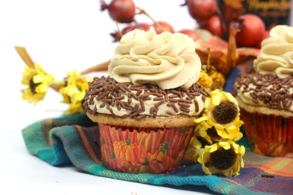 Pumpkin Spice Cupcakes with Buttercream Frosting Recipe and chocolate sprinkles on a multi-colored checkered cloth next to some yellow flowers