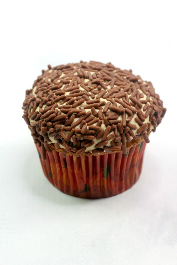 a pumpkin spice cupcake with buttercream frosting topped with chocolate sprinkles